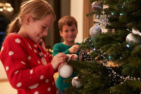 christmas fun: Children Decorating Christmas Tree At Home Stock Photo