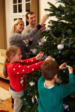 家族一緒に自宅のクリスマス ツリーを飾る