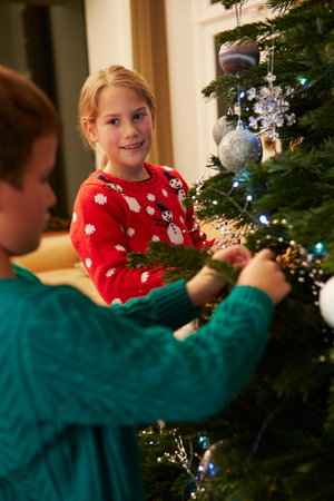decorating christmas tree: Children Decorating Christmas Tree At Home Stock Photo