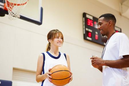 high school basketball: Female High School Basketball Player Talking With Coach
