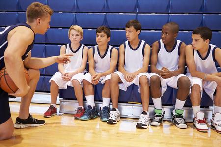コーチとチームの話を有する男性高校バスケット ボール チーム