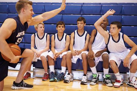 high school basketball: Male High School Basketball Team Having Team Talk With Coach Stock Photo