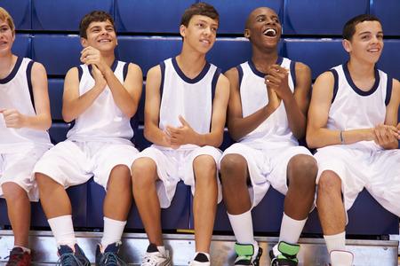 high school basketball: Members Of Male High School Basketball Team Watching Match