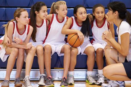 Coach Van Vrouwelijke High School Basketball Team Geeft Team Talk Stockfoto