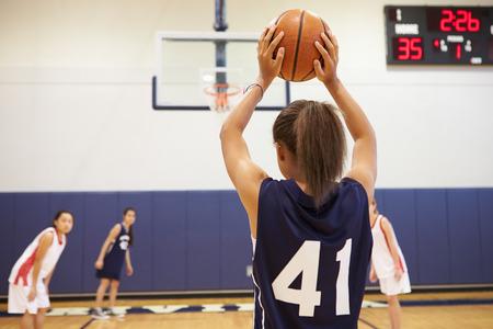 high school sports: Female High School Basketball Player Shooting Basket Stock Photo
