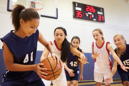 Female High School Basketball Team Playing Game Foto de archivo