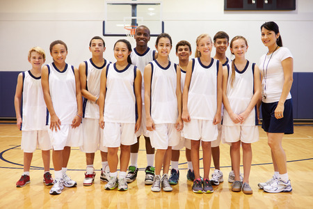 school sports: Portrait Of High School Sports Team In Gym With Coach Stock Photo