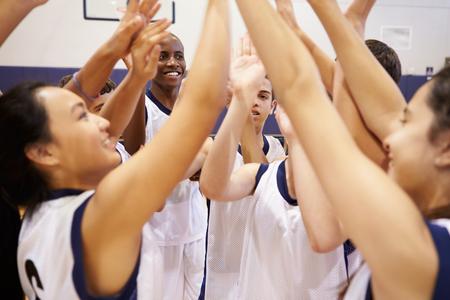 school gym: High School Sports Team Celebrating In Gym