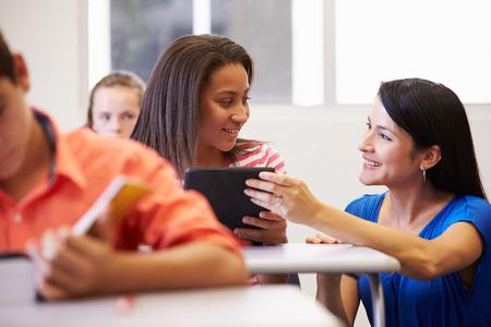 highschool students: Teacher Helping Female High School Student In Classroom