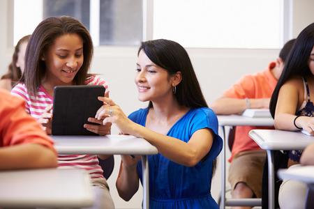 salle de classe: Enseignant Aider Female Student High School en salle de classe Banque d'images