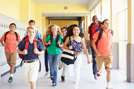 12 13: Group Of High School Students Running Along Corridor