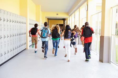 escuelas: Grupo de estudiantes de secundaria ejecuta a lo largo del Corredor