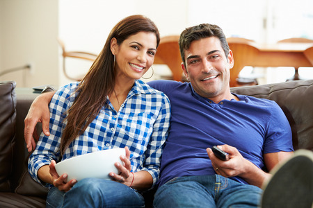 Couple Sitting On Sofa Watching TV Together photo