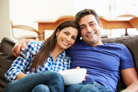 mid adult couple: Couple Sitting On Sofa Watching TV Together Stock Photo