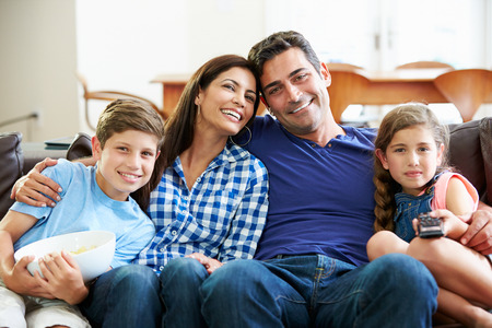 Familia que se sienta en un sofá viendo la televisión juntos