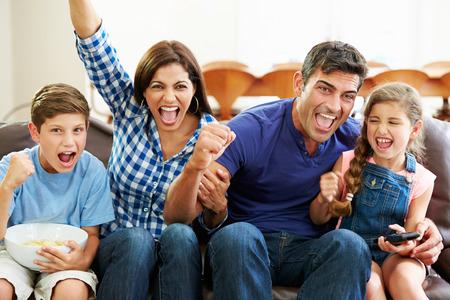 Familie kijken naar voetbal vieren doel Stockfoto