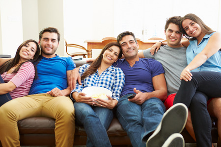group goals: Group Of Friends Sitting On Sofa Watching TV Together