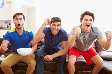merienda: Grupo de hombres sentados en el sof� viendo el deporte Juntos