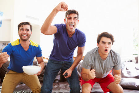 snacks: Group Of Men Sitting On Sofa Watching Sport Together