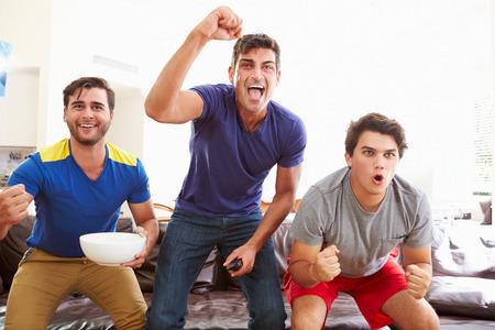 personas viendo television: Grupo de hombres sentados en el sofá viendo el deporte Juntos