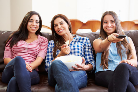 Group Of Women Sitting On Sofa Watching TV Together photo