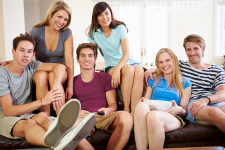 watching football: Group Of Friends Sitting On Sofa Watching TV Together