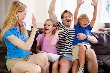 Family Watching Soccer on TV Celebrating Goal photo