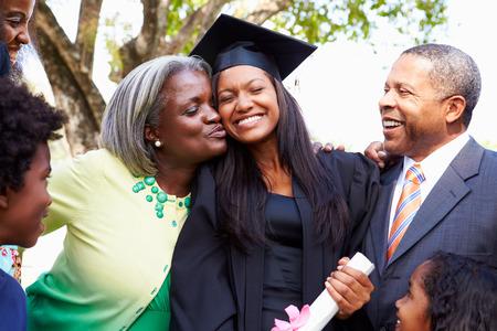 graduado: Estudiante celebra la graduaci�n con los padres Foto de archivo