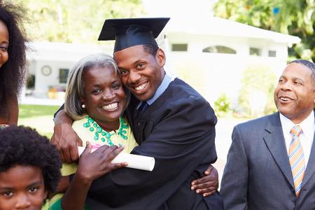 mama e hijo: Estudiante celebra la graduación con los padres Foto de archivo