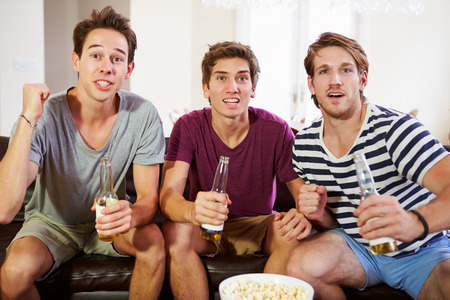 tense: Group Of Men Sitting On Sofa Watching Sport Together