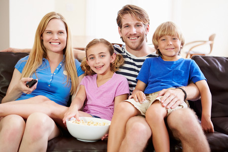 Family Sitting On Sofa Watching TV Together photo