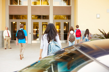 High School Students Being Dropped Off At School By Parents Stock Photo
