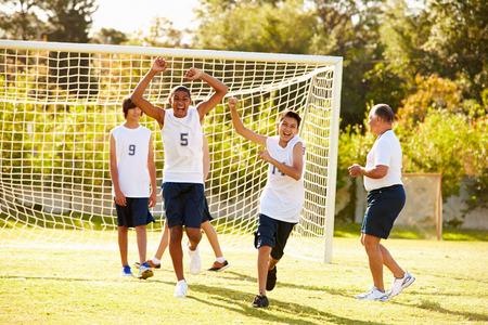 group goals: Player Scoring Goal In High School Soccer Match Stock Photo
