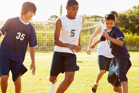 match: Mitglieder der männlichen Schule Fußball spielen Spiel