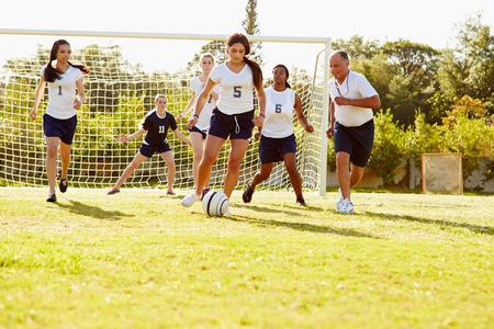 school sports: Members Of Female High School Soccer Playing Match