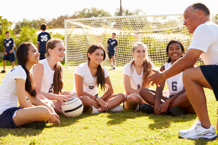 soccer pitch: Coach Giving Team Talk To Female High School Soccer Team Stock Photo