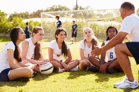 females: Coach Giving Team Talk To Female High School Soccer Team Stock Photo