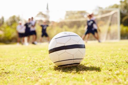 バック グラウンドでの選手とサッカー ボールのクローズ アップ 写真素材