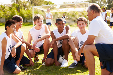 uniform student: Coach Giving Team Talk To Male High School Soccer Team