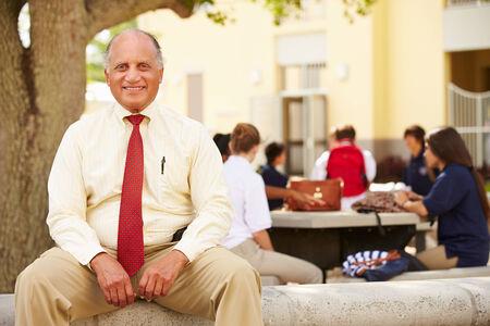 high school teacher: Portrait Of High School Teacher Sitting On School Campus