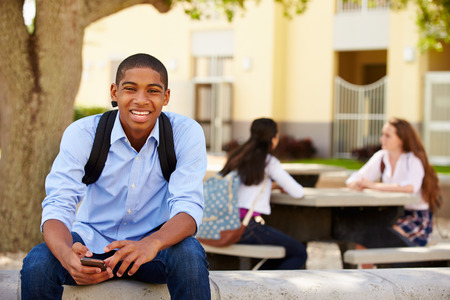 smiling teenagers: Male High School Student Using Phone On School Campus