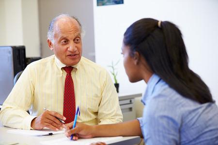 entrevista: Estudiante femenino que hablan con el consejero de la preparatoria Foto de archivo
