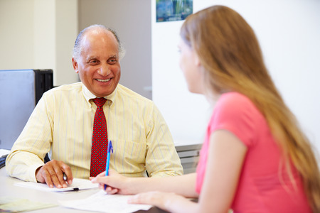 Estudiante femenino que hablan con el consejero de la preparatoria