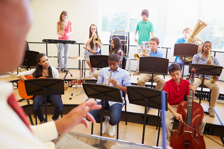 Pupils Playing Musical Instruments In School Orchestra photo