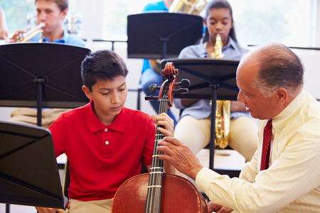 american music: Boy Learning To Play Cello In High School Orchestra