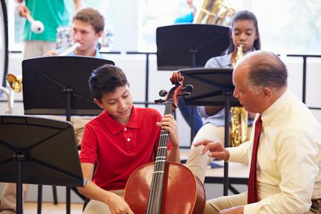 高校オーケストラでチェロを弾くことを学ぶの少年