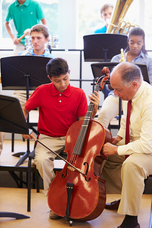 musical instrument: Boy Learning To Play Cello In High School Orchestra