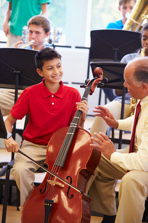 female student: Boy Learning To Play Cello In High School Orchestra
