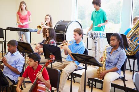 escuelas: Los alumnos que tocan los instrumentos musicales en la Orquesta Escuela Foto de archivo