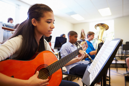 school band: Female Pupil Playing Guitar In High School Orchestra
